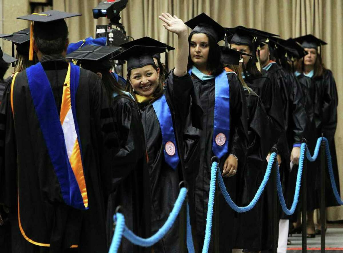 A graduate waves to her supporters during UTSA's Spring commencement ceremonies for the College of Education and Human Development at the Convocation Center at the 1604 Campus on Friday, May 6, 2011. Kin Man Hui/kmhui@express-news.net