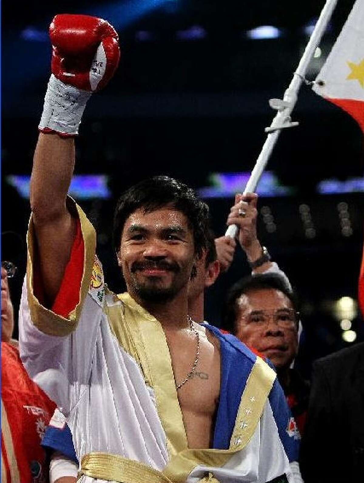 Manny Pacquiao celebrates after last November's victory over Antonio Margarito at Cowboys Stadium in Arlington. For that fight, Pacquiao chartered a 747 to fly in 200 friends and relatives from the Philippines. NICK LAHAM/GETTY IMAGES