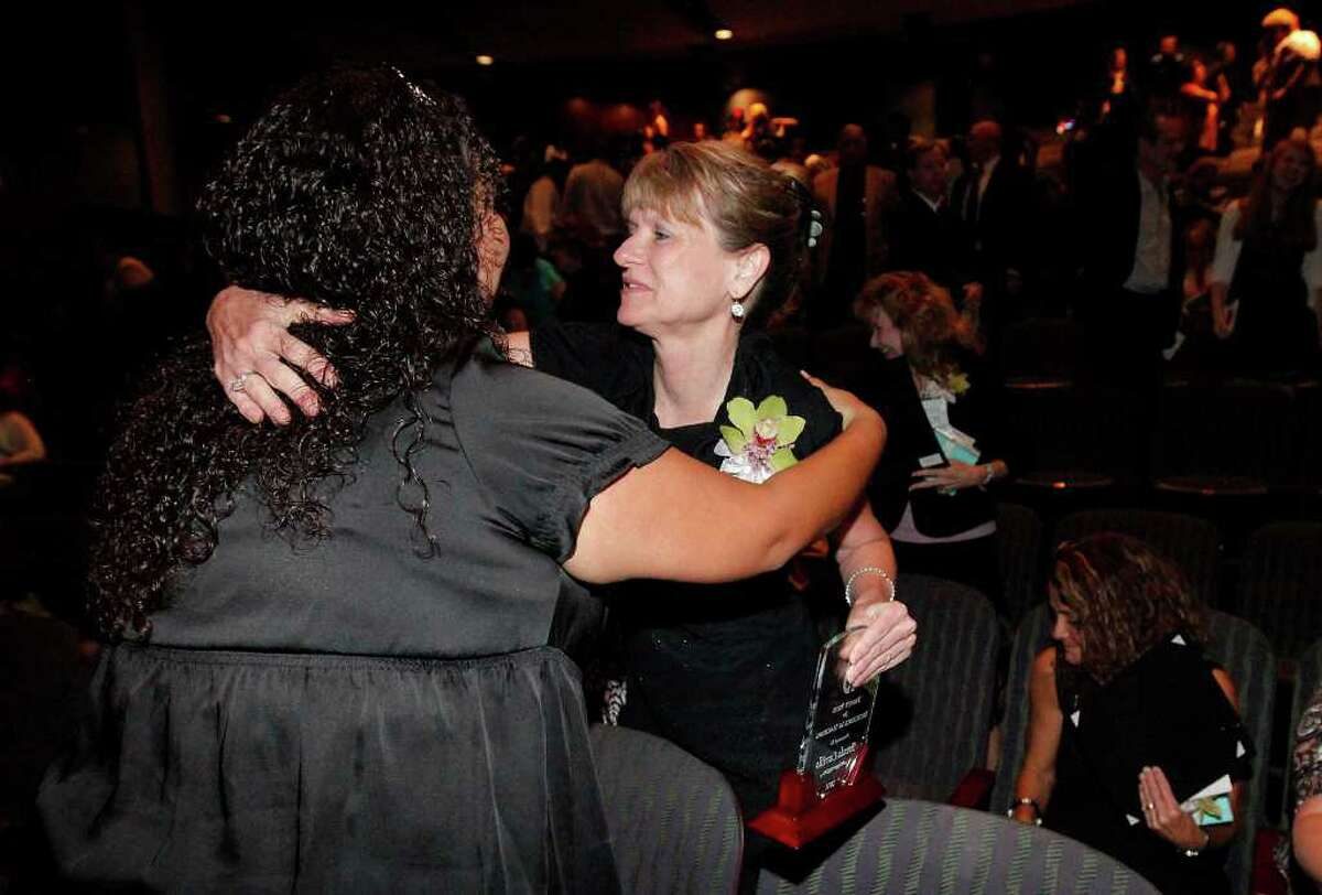 Brenda Carrillo (center) receives a hug from Leslie Ann Garza after Carrillo was awarded the Trinity Prize for Excellence in Teaching at Trinity University on Friday, May 6, 2011. Carrillo was joined by 19 area educator finalists and only one of two to receive the $2,500 prize and recognition for her work in the classroom. Carrillo has been an educator for 28 years and teaches biology at McCollum High School of which she is also an alumni. Kin Man Hui/kmhui@express-news.net
