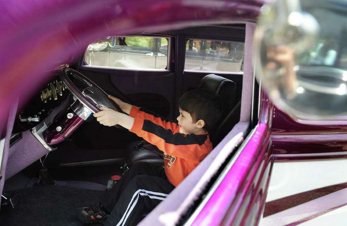 Dylan Lehning, 5, sits in the driver's seat of a 1934 Ford owned by Robert Papstein, of Westport, during the 8th Annual Model Ts to Mustangs Antique and Classic Car Show at the Stamford Museum and Nature Center in Stamford, Conn. on Saturday May 7, 2011.