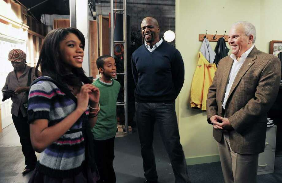 "Actor and former NFL player Terry Crews, center, on the set of ""Are We There Yet"" with former Lt. Governor Michael Fedele and cast members Teala Dunn, 14, and Coy Stewart, 12. Crews was spotted at the North Mianus School Pow Wow last weekend with his wife, Rebecca, and their children. Photo: Kathleen O'Rourke, ST / Stamford Advocate"