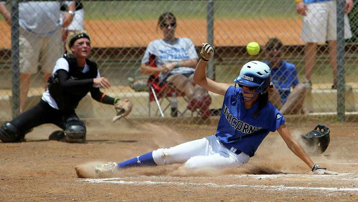 New Braunfels' Jade Smith beats the throw to home plate by East Central catcher Brittany Covert (left) to score a run in the fifth inning in softball at East Central on Saturday, May 7, 2011. New Braunfels clinched a playoff victory winning 6-2 in game 2. Kin Man Hui/kmhui@express-news.net