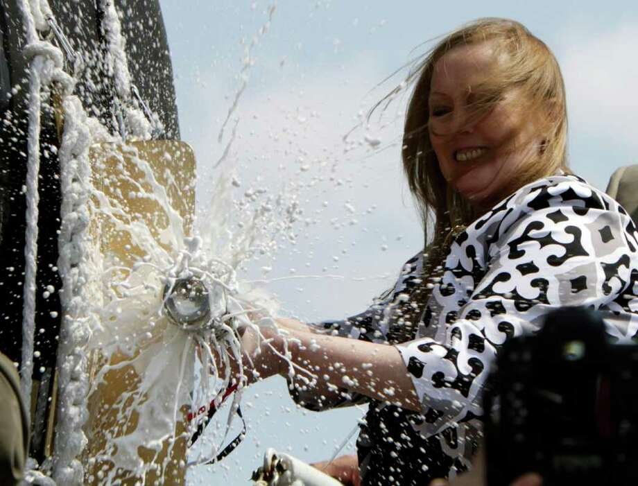 """Maureen Murphy, mother of  Medal of Honor recipient and U.S. Navy SEAL, Lt.  Michael Murphy, christens the ship baring his name during a ceremony at the Bath Iron Works shipyard in Bath, Maine on Saturday, May 7, 2011, what would've been Murphy's 35th birthday. The mother of a Navy SEAL from Maine killed in Afghanistan said """"Happy birthday, baby"""" before smashing a bottle of Champagne against a Navy ship that bears her son's name. (AP Photo/Pat Wellenbach) Photo: Pat Wellenbach"""