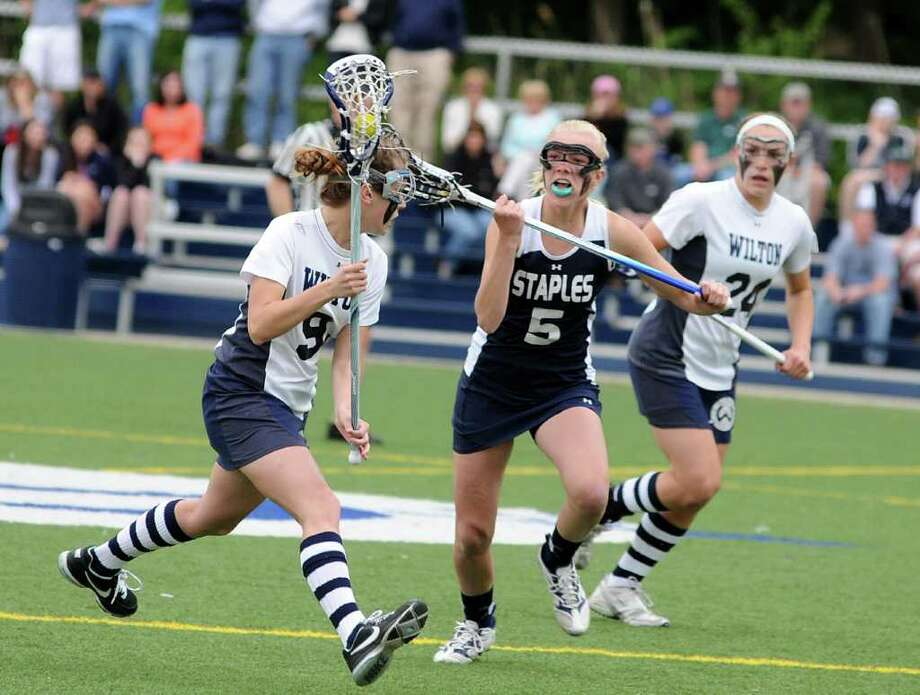 Wilton's Maddie McClintock, left, has possession of the ball while Staples' Ryan Kirschner, center,  and Wilton's Casey Pearsail follow closely behind during agirls lacrosse game Staples vs Wilton at Wilton on Saturday May 7, 2011. Photo: Lisa Weir / The News-Times Freelance