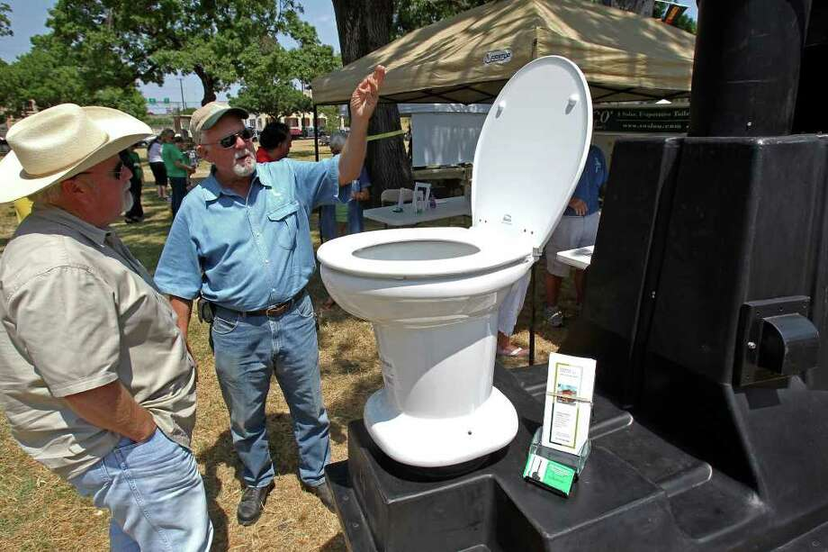 George Witta (right) explains the workings of the EnviroLoo toilet to homebuilder Mark Fahnert at Solar Fest. Tom Reel/Staff Photo: Tom Reel, San Antonio Express-News / © 2011 San Antonio Express-News