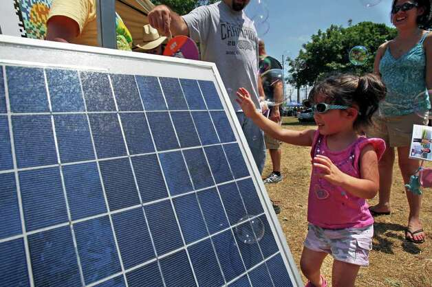 Lorelei Dooley, 3, tries to catch bubbles emerging from the back of a solar collector panel at the Soalr San Antonio booth as Solar Fest  takes place in Maverick Park on May 7, 2011.    Tom Reel/Staff Photo: Tom Reel, San Antonio Express-News / © 2011 San Antonio Express-News
