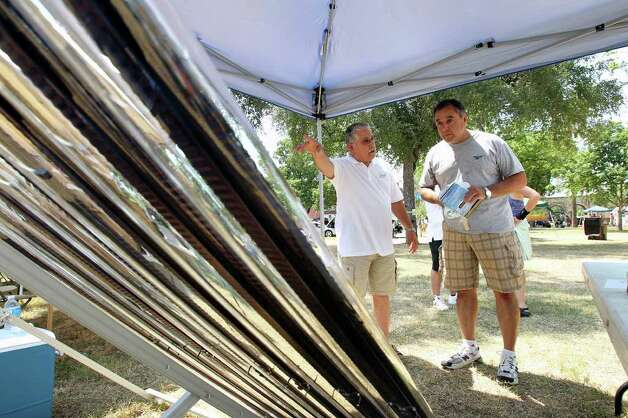 Marko Mendez (left) shows off his solar evacuated thermal tube array to prospective buyer Abel Videl as Solar Fest  takes place in Maverick Park on May 7, 2011.  The system is designed for use in water heating in domestic applications and also for air conditioning and heating applications. Photo: Tom Reel, San Antonio Express-News / © 2011 San Antonio Express-News