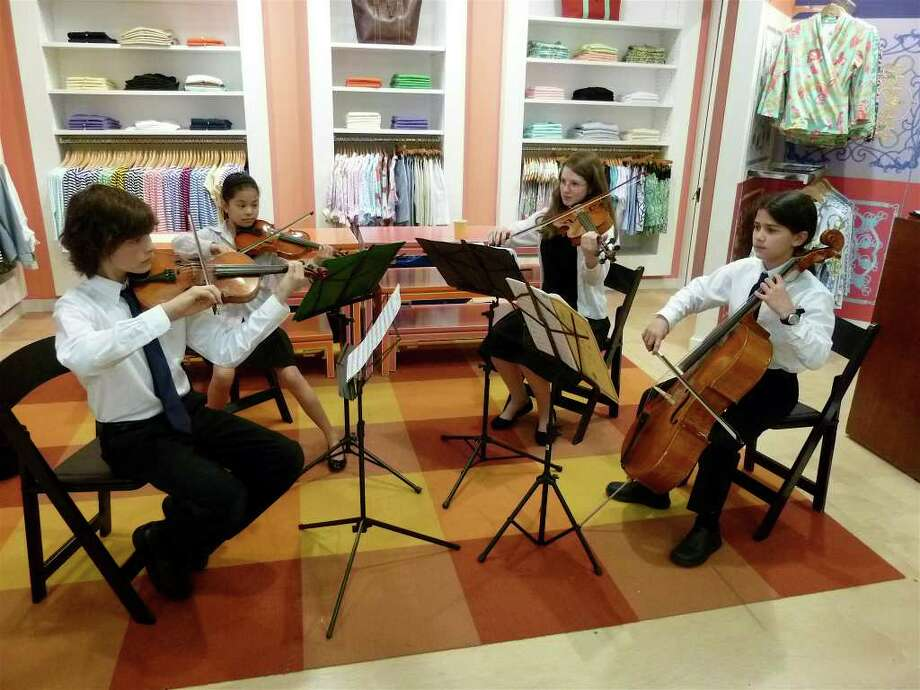 A quartet of young musicians performs at J. McLaughlin store, which hosted a fundraiser for Music For Youth. Pictured, from left, are 11-year-olds Declan Cummiskey, Olivia Owens, Michelle Curtis and Lance Parisot. Photo: Contributed Photo/Mike Lauterborn / Westport News contributed