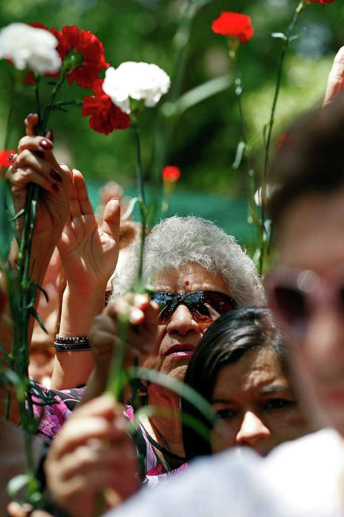 METRO - Alicia Anzaldua Salinas, 74, wearing glasses, holds up her carnation along with other mothers during a blessing after the Mother's Day Mass at Our Lady of Lourdes Grotto, Sunday, May 8, 2011. JERRY LARA/glara@express-news.net