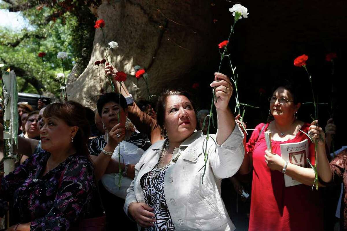 METRO -- Holding up her carnation and glancing at an icon of the Virgin Mary, Victoria Sanchez, 50, center, participates in a blessing as she and other faithful gather for a Mother's Day Mass at Our Lady of Lourdes Grotto, Sunday, May 8, 2011. JERRY LARA/glara@express-news.net