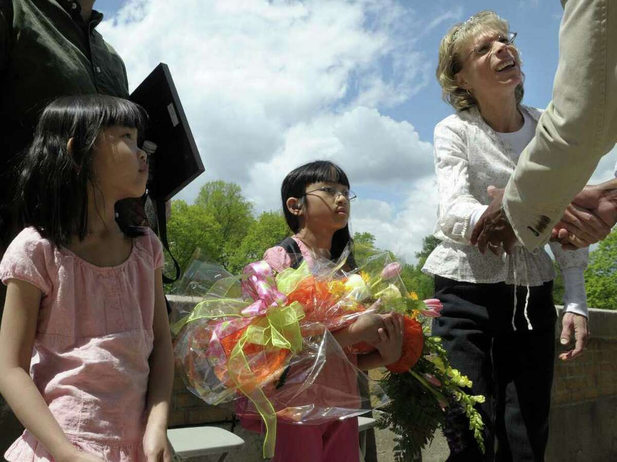 Mei Lei Urbanski, left, 6, and her sister, Jenna, 8, look on as their mom Juliann Urbanski shakes hands with people congratulating her after she won the Tulip Festival Mother of the Year Award during the Tulip Festival at Washington Park on Sunday afternoon, May 8, 2011 in Albany. (Paul Buckowski / Times Union)