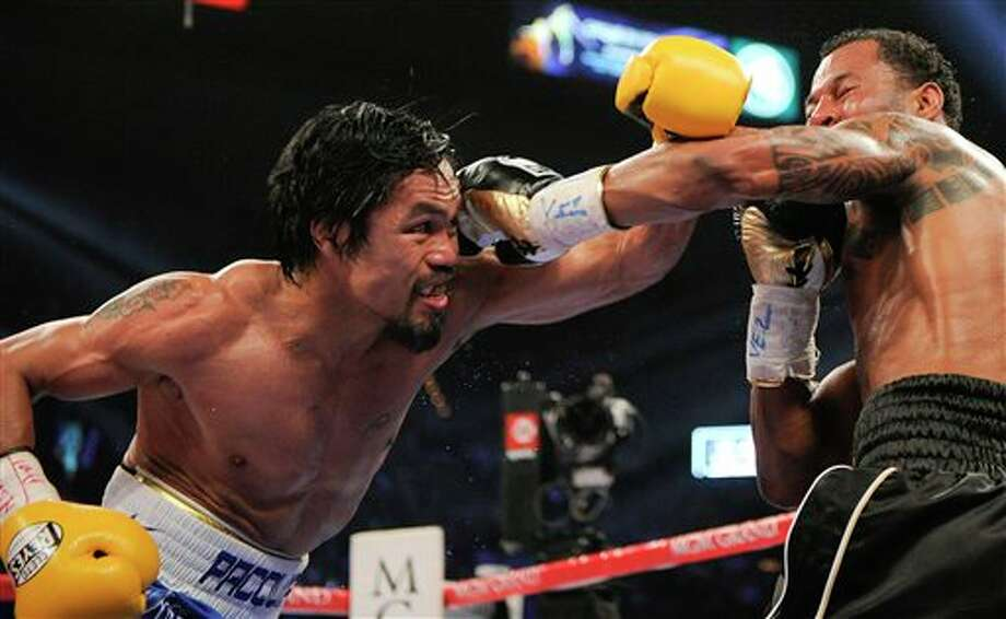 Manny Pacquiao, left, throws a punch against Shane Mosley in the fourth round during a WBO welterweight title bout, Saturday, May 7, 2011, in Las Vegas.  (AP Photo/Mark Terrill) Photo: Mark Terrill, Associated Press / AP2011