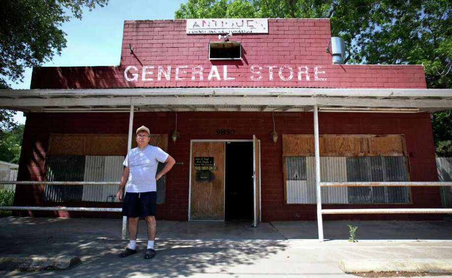 John Roof stands in front of his art studio, General Store Restoration Shop, which is also where he lives, in Staples. He has one of only two businesses in the small town, where two miles away the Texas 130 toll road is being built. Photo: BOB OWEN, Bob Owen/Express-News / rowen@express-news.net