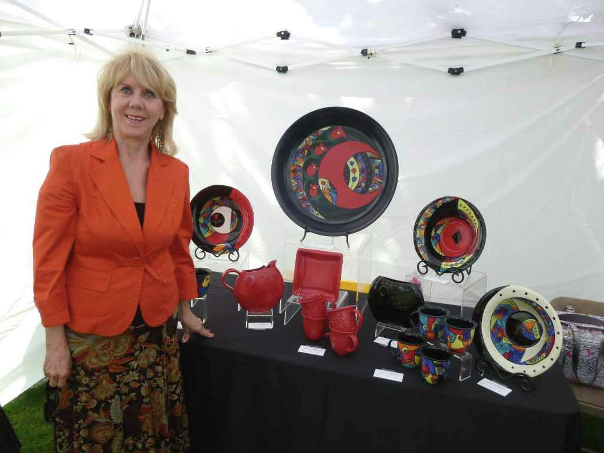 Lois Barker, of Jean Elton Studio in Fairfield, displays platters, cups and dinnerware at the Fairfield Woman's Club Crafts Fair on Town Hall Green.