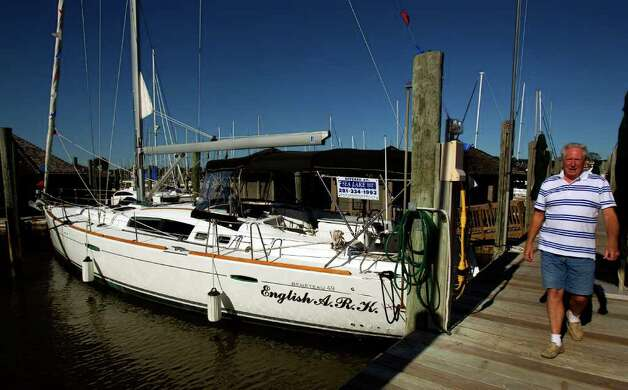 Pat O'Neal with Sea Lake Yacht Sales walks past a Beneteau 49 yacht that is ...
