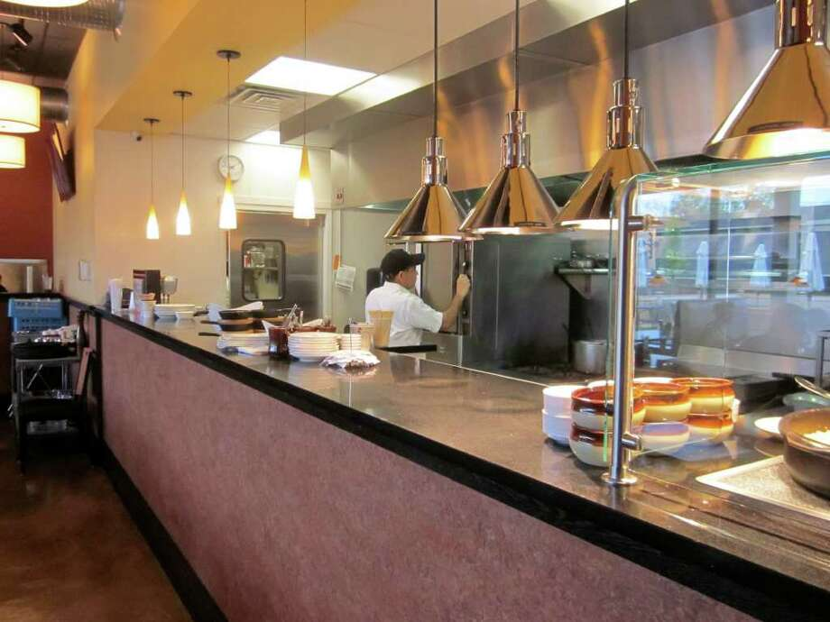 Phil's Grill features an open-kitchen design that allows diners to watch as their food is being prepared. - Photo by John H. Palmer Photo: File Photo / Darien News