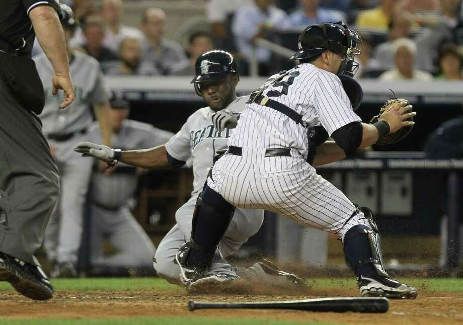 NEW YORK - JUNE 29: Milton Bradley #15 of the Seattle Mariners slides safely into home under the tag of Francisco Cervelli #29 of the New York Yankees at Yankee Stadium on June 29, 2010 in the Bronx borough of New York City.  (Photo by Nick Laham/Getty Images) *** Local Caption *** Milton Bradley Photo: Nick Laham, Getty Images / 2010 Getty Images