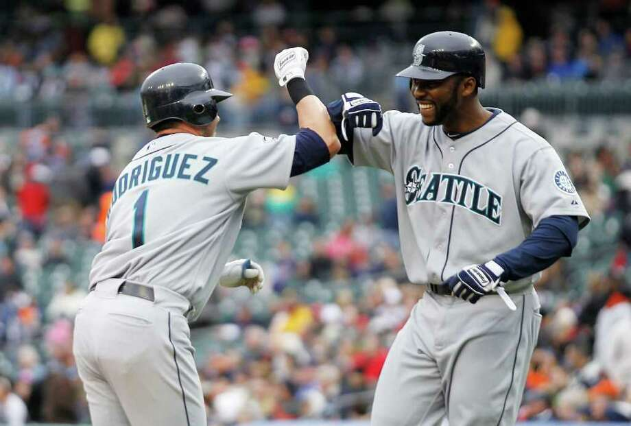 DETROIT - APRIL 28:  Luis Rodriguez #1 of the Seattle Mariners hits a three run home run in the eigth inning and is congratulated by teammate Milton Bradley #15 during the game against the Detroit Tigers at Comerica Park on April 28, 2011 in Detroit, Michigan. The Mariners defeated the Tigers 7-2.  (Photo by Leon Halip/Getty Images) *** Local Caption *** Luis Rodriguez;Milton Bradley; Photo: Getty Images