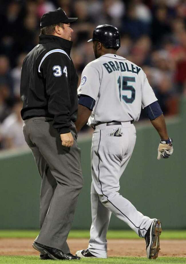 BOSTON, MA - APRIL 30:  Milton Bradley #15 of the Seattle Mariners walks past Sam Holbrook #34 and heads to the dugout after he is thrown out of the game against the Boston Red Sox on April 30, 2011 at Fenway Park in Boston, Massachusetts.  (Photo by Elsa/Getty Images) *** Local Caption *** Milton Bradley;Sam Holbrook; Photo: Getty Images
