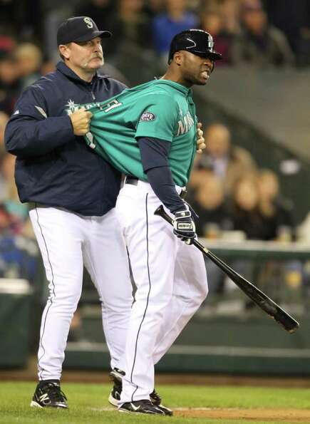 SEATTLE - MAY 06:  Milton Bradley #15 of the Seattle Mariners is restrained by manager Eric Wedge #2