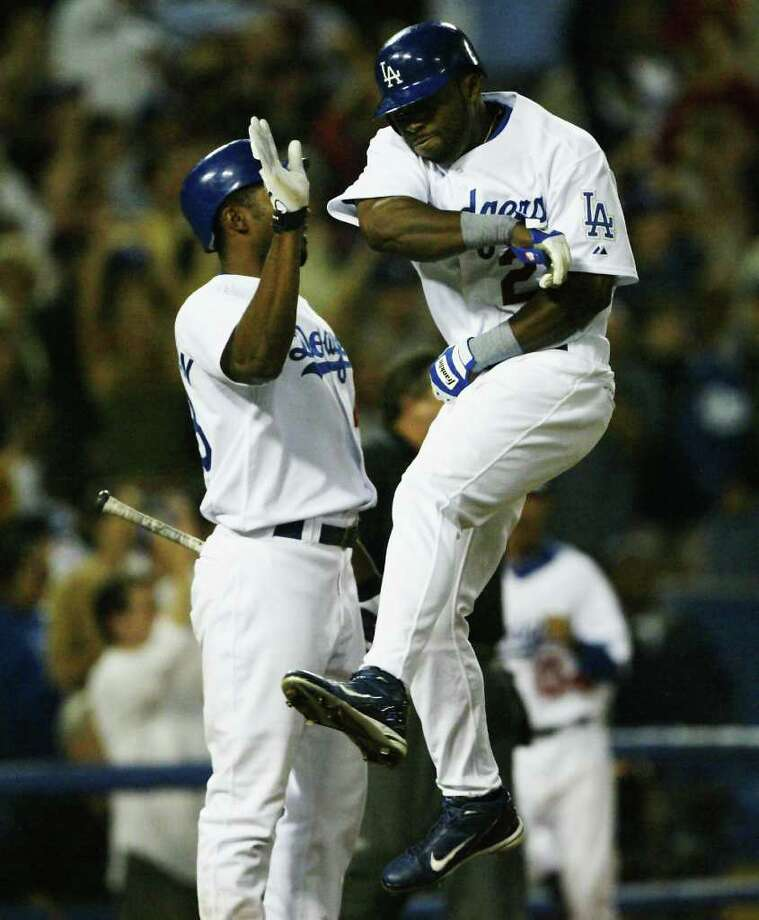 LOS ANGELES - JULY 1:  Milton Bradley #21 of the Los Angeles Dodgers jumps to celebrate as he crosses the plate to score the go ahead and eventual winning run against the San Francisco Giants as Juan Encarnacion #43 greets him on July 1, 2004 at Dodger Stadium in Los Angeles, California. Photo: Stephen Dunn, Getty Images / 2004 Getty Images