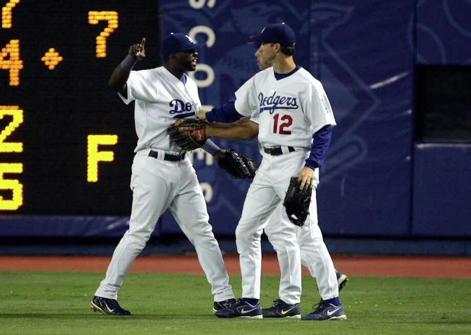 LOS ANGELES - SEPTEMBER 28:  Right fielder Milton Bradley #21 of the Los Angeles Dodgers is restrained by Steve Finley #12 and Alex Cora after an incident with a fan after Bradley's error against the Colorado Rockies allowed two runs to score in the eighth inning on September 28, 2004 at Dodger Stadium in Los Angeles, California. Photo: Stephen Dunn, Getty Images / 2004 Getty Images