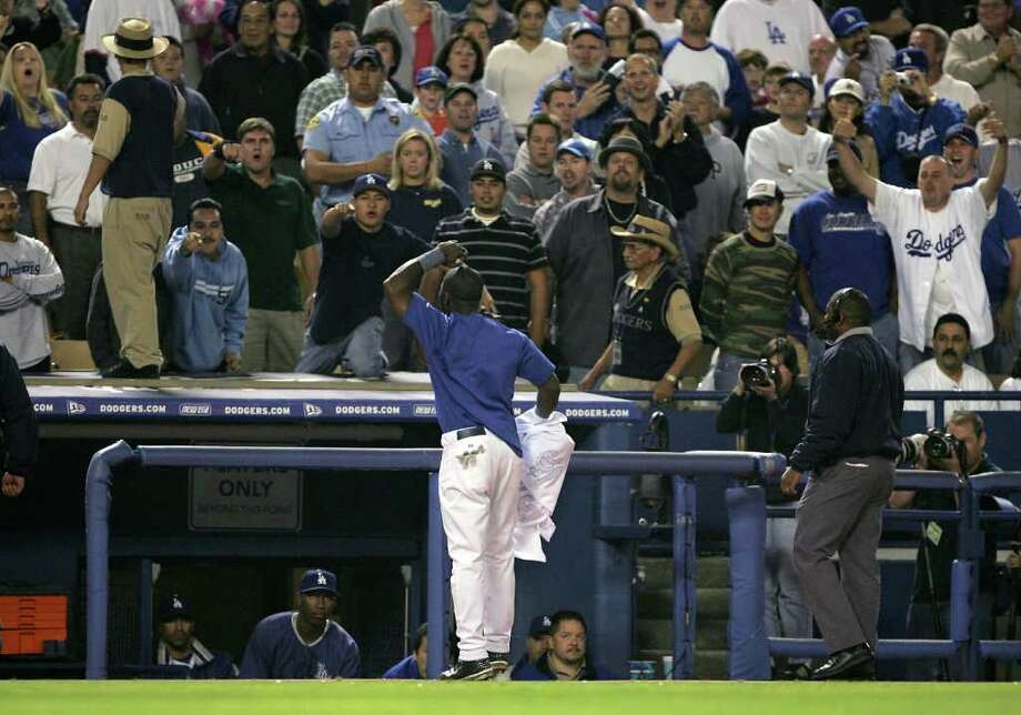 LOS ANGELES - SEPTEMBER 28:  Right fielder Milton Bradley #21 of the Los Angeles Dodgers gestures to the fans over the Dodgers dugout as he leaves the field following an incident with a fan in right field after Bradley's error against the Colorado Rockies allowed two runs to score in the eighth inning on September 28, 2004 at Dodger Stadium in Los Angeles, California. Photo: Stephen Dunn, Getty Images / 2004 Getty Images