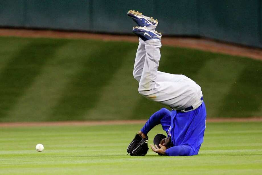 HOUSTON - APRIL 06:  Milton Bradley #21 of the Chicago Cubs flips over after missing a fly ball against the Houston Astros on Opening Day on April 6, 2009 at Minute Maid Park in Houston, Texas.  The Cubs defeated the Astros 4-2.  (Photo by Chris Graythen/Getty Images) *** Local Caption *** Milton Bradley Photo: Chris Graythen, Getty Images / 2009 Getty Images
