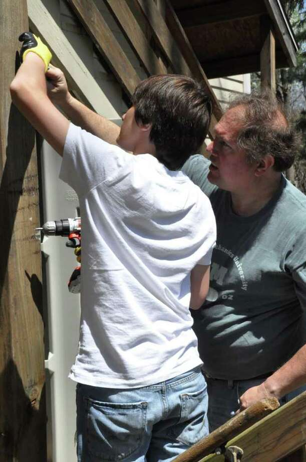 The father-and-son team of Bruce and Connor Mitnick work closely while installing install a shed for Project Return. Photo: Contributed Photo / Westport News