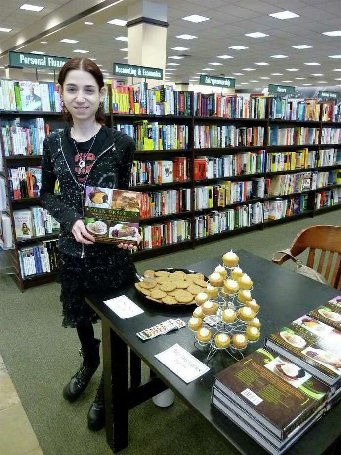 """Author Hannah Kaminsky poses at the Barnes & Noble bookstore in Westport with a copy of her new book """"Vegan Desserts: Sumptuous Sweets for Every Season."""" Photo: Contributed Photo/Mike Lauterborn / Westport News contributed"""