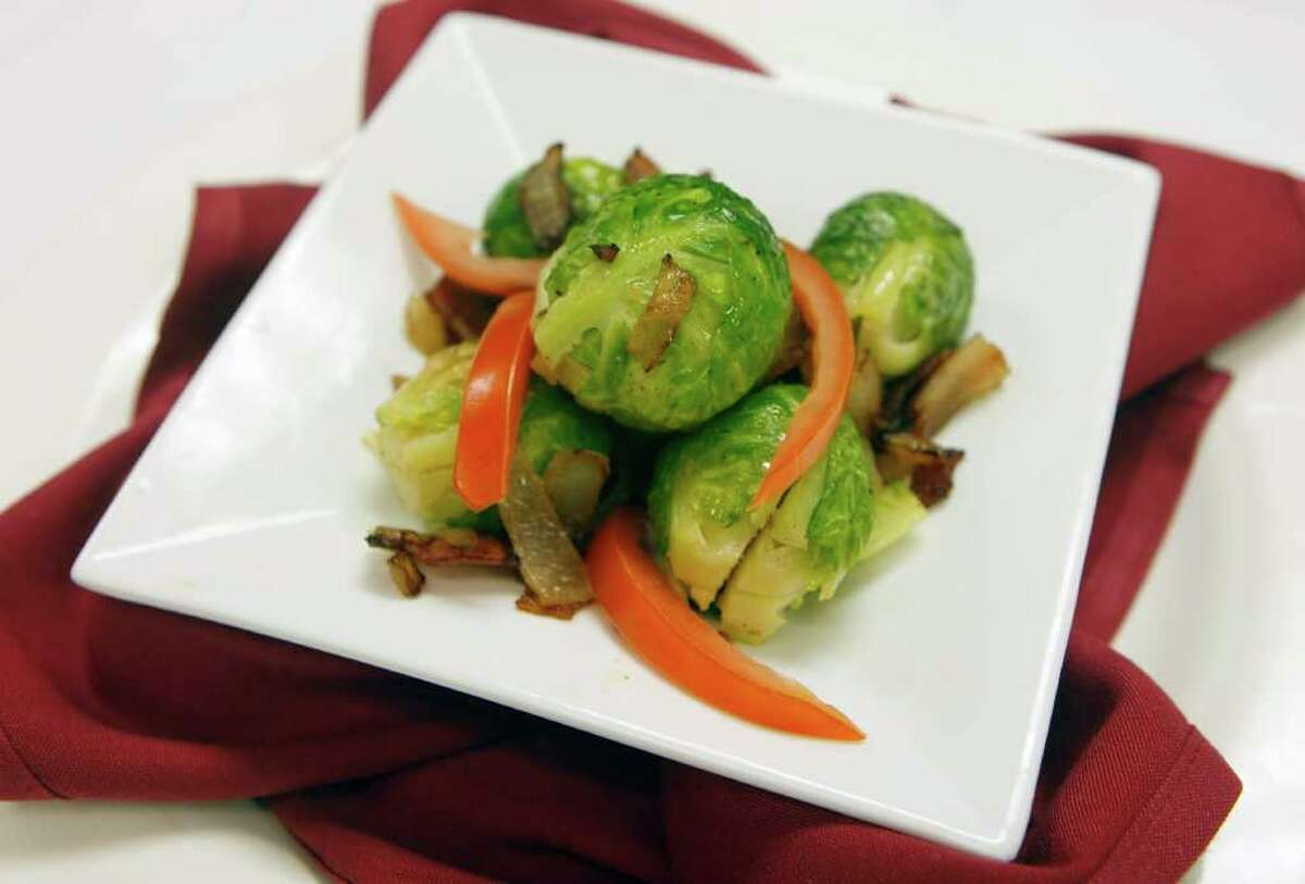 """Chef James """"Jimmy"""" Strikos serves Brussels sprouts with bacon and onion at Oak Hills Country Club."""
