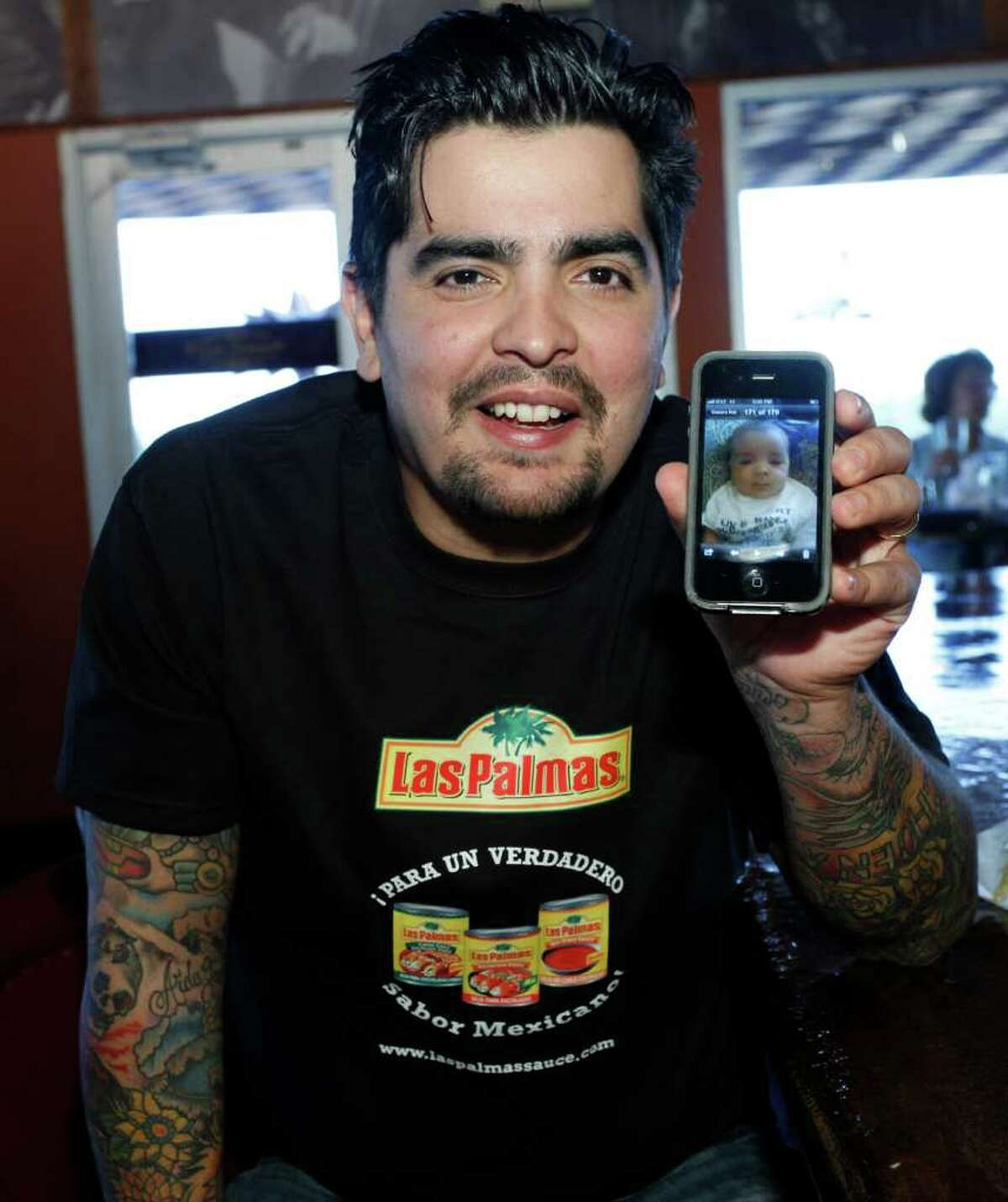Sánchez shows a photo of his 7-month-old son on his smartphone.
