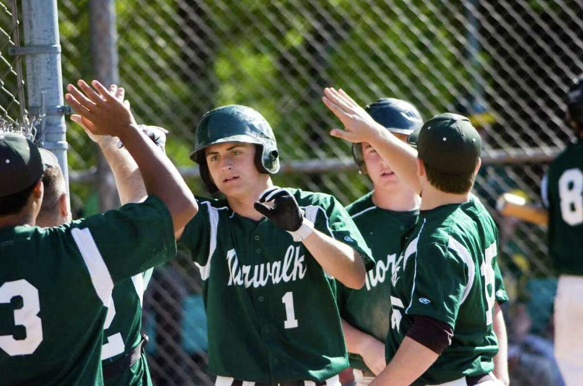 Norwalk's James Cooksey is greeted by teammates after bringing a run home as Trinity Catholic hosts Norwalk High School in a baseball game in Stamford, Conn., May 9, 2011. Norwalk won the game 17-1.