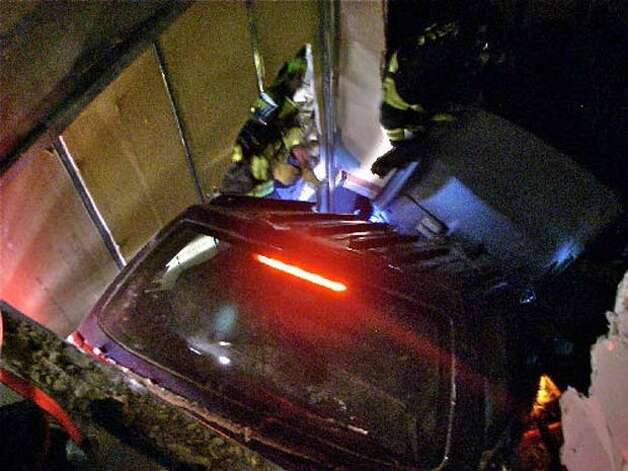 Seattle firefighters work to remove the car of a woman who drove through a wall and went down roughly 10 feet. (Seattle Fire Department photo)