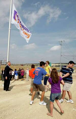 Gordon Hartman (left) guides special needs students as they raise the flag for the Monarch Academy. The school, for special needs students, will sit on 2.3 acres next to the 25-acres Morgan's Wonderland. It is scheduled to open this August 22 and will start with a student body of 35. It is accepting applications for students between the sixth grade and 18 years of age as of Sept. 1, 2011. Although construction for the school is just starting, classes will begin in portable buildings. JERRY LARA/glara@express-news.net Photo: JERRY LARA, Jerry Lara/Express-News / SAN ANTONIO EXPRESS-NEWS