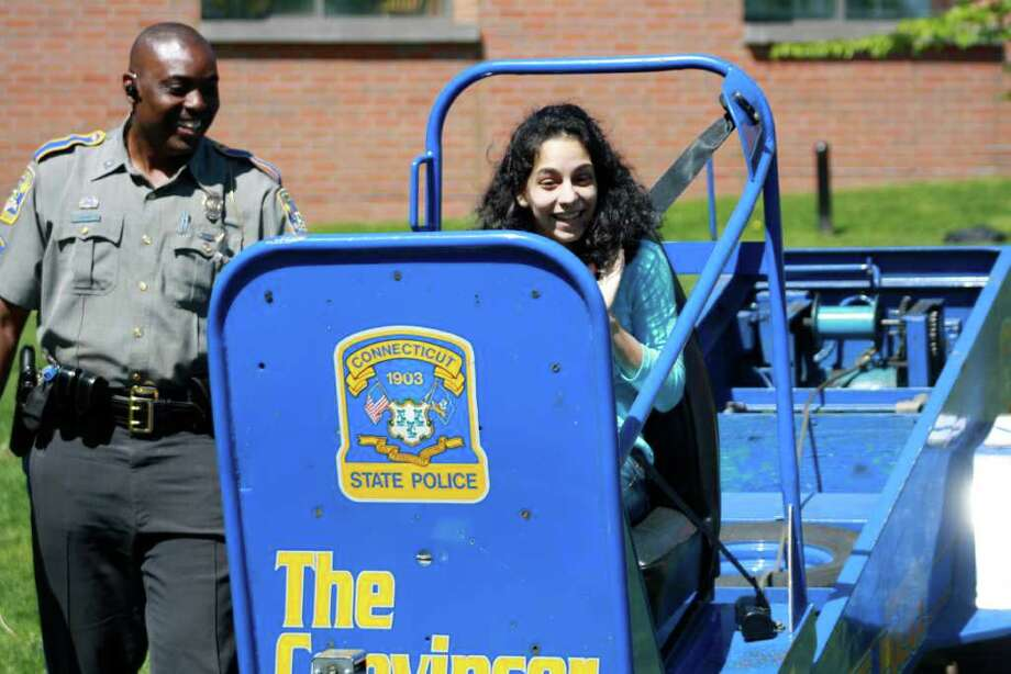 Darien High School Senior Cindy Gaete gets ready to experience what an accident at 5 mph. would feel like as State Trooper Chris Davis watches. Photo: Contributed Photo / Darien News