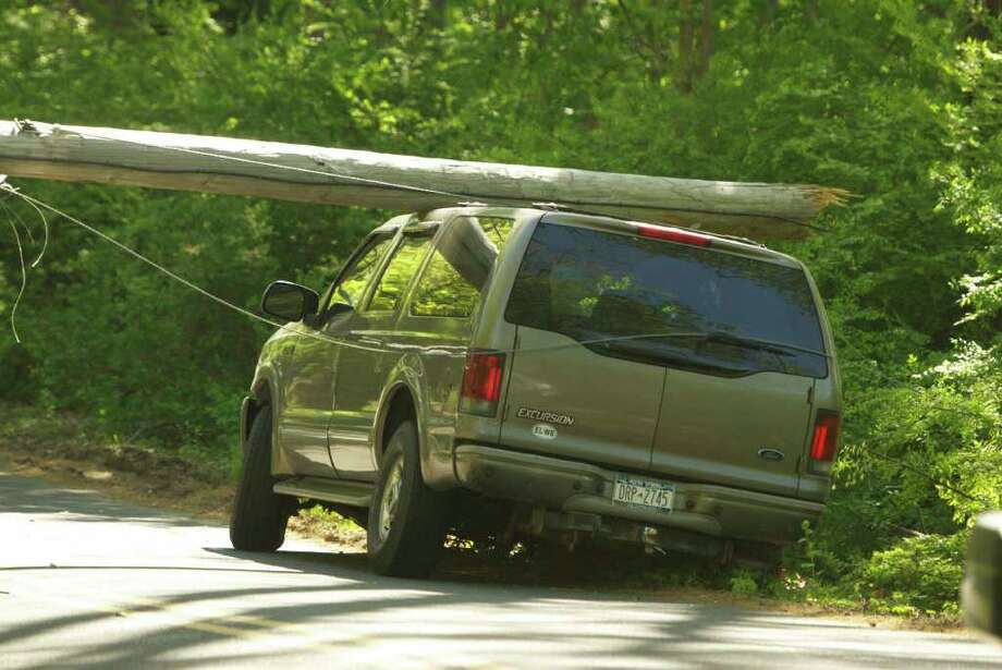 A Ford Expedition struck a pole on Dingletown Road Tuesday, causing it to fall on top of the vehicle. None of the six passengers inside the vehicle were injured, according to police. Photo: John Ferris Robben / Greenwich Time