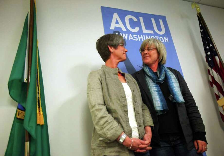 Major Margaret Witt, who was dismissed from the Air Force under the Don't Ask, Don't Tell policy, stands with her partner Laurie McChesney, left, as Witt announces her settlement with the Air Force on Tuesday, May 10, 2011 at the ACLU of Washington office in Seattle. Witt, a decorated flight nurse, will retire with full benefits and an unlawful discharge will be removed from her record. Photo: JOSHUA TRUJILLO / SEATTLEPI.COM