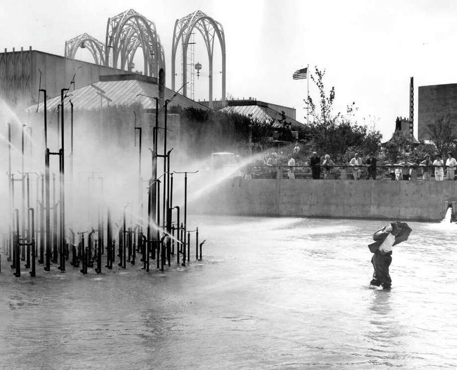 Dale Pierce, plumber, pulls rubber jacket over his head as he walks away from spray from new Center fountain after adjusting sprinkler heads. July 3, 1963. (seattlepi.com file photo) Photo: Seattlepi.com File / Seattle Post-Intelligencer