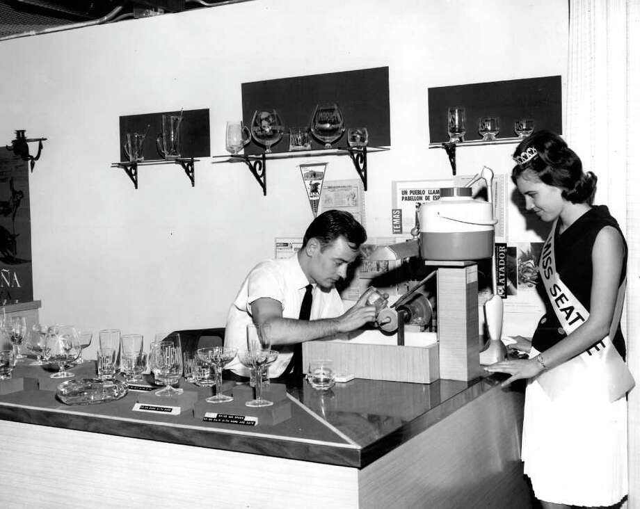 Kristine Hansen, Miss Seattle, looks on as Mr. Arribas of the Spanish exhibit cuts glass. May 16, 1966. (seattlepi.com file photo) Photo: Seattlepi.com File / Seattle Post-Intelligencer