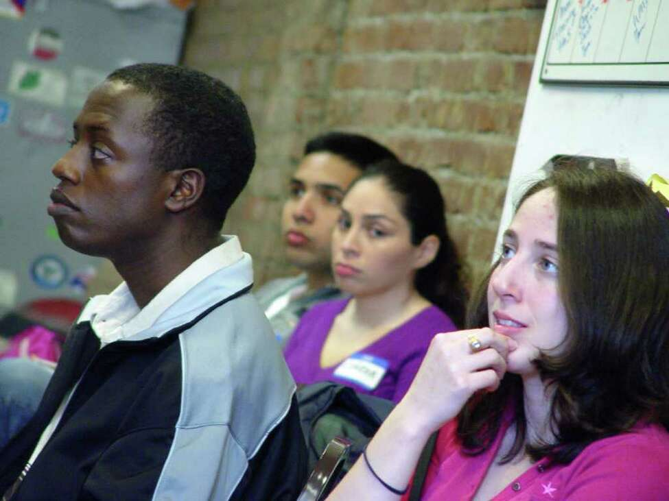 Albany residents Olivier Mandevu, left, and Lauren Keeley, right, listen to presenters during medical interpreter training conducted by MAMI Interpreters. Keeley is fluent in Spanish and Mandevu speaks French, Swahili, Kinyamulenge, Kinyarwarwanda and Kirundi. (Courtesy St. Peter?s Hospital)