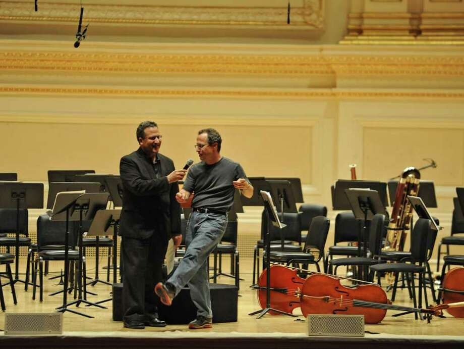 "Conductor David Alan Miller, right, kicks his leg in a ""New York, New York""  fashion and says ""If you can make it there, you'll make it anywhere"" during an interview after the Albany Symphony Orchestra finished their rehearsal before it's debut concert at Carnegie Hall in NEW YORK Tuesday May 10, 2011. (Lori Van Buren / Times Union) Photo: Lori Van Buren"