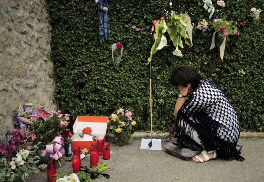 A woman mourns the passing of Seve Ballesteros on Wednesday near tributes placed outside his house in Pedrena, Spain. Photo: Alvaro Barrientos, Associated Press