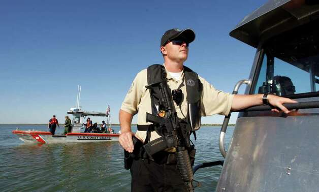 Texas game warden Jake Mort, armed with an M-16, and Coast Guard officials patrol Falcon Lake in the wake of the death of David Hartley. Photo: Associated Press File Photo