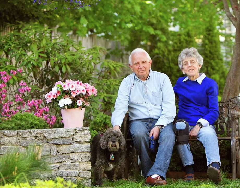 Dr. Robert and Robin DeMartin, one of last year's first-place winners, sit in the garden at their home on Orchard Park with their dog Parker. Photo: Contributed Photo