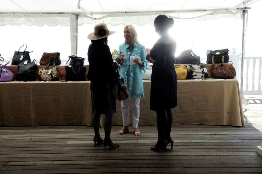 From left, Laurel Fedor, Valerie Wallace and Lillian Ankrah at the YWCA Greenwich Old Bags Luncheon to raise funds for the fight against domestic violence at the Belle Haven Club on Thursday, May 12, 2011. Photo: Helen Neafsey / Greenwich Time