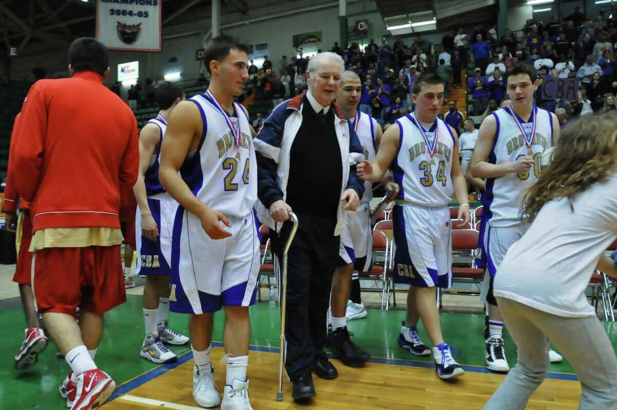 CBA players Joshua Dennis, left, and Zach Zaloga, 34, right, escort Brother Aloysius Myers to the court to join a team group picture as they celebrate their Class AA state basketball championship game victory over Half Hallow Hills West, 71-53, at the Glens Falls Civic Center in Glens Falls, NY, on Sunday, March 21, 2010. The team held up the picture so that the Brother could join them. Brother Aloysius died this week. (Philip Kamrass / Times Union) High School Sports