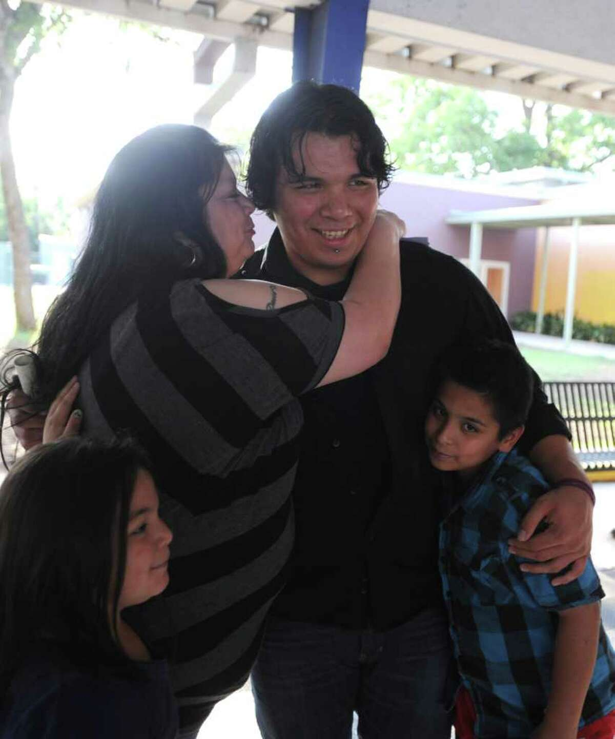 Alexander Vidales receives congratulations from his mother, Laura Aguilar, and his siblings, Iris and Moses.