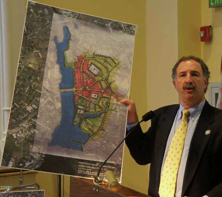 State Rep. Jonathan Steinberg holds up a map of Westport downtown highlighting prospective changes to the area during a Thursday forum sponsored by the Planning and Zoning Commission. Photo: Paul Schott / Westport News