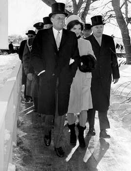 In this Jan. 20, 1961, black and white file photo, President John F. Kennedy and wife Jacqueline Kennedy walk outside the White House during inauguration ceremonies, just as the parade began. Photo: AP